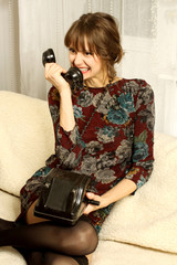 Girl in evening dress emotional talking on old phone