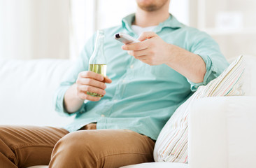 man with beer and remote control at home
