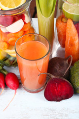 Jar of cut vegetables and glass of fresh carrot juice with