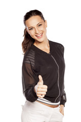 happy young woman with thumb up on white background
