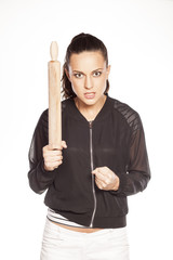 angry young woman standing with a rolling pin in her hands