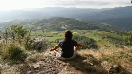 man sitting at the top of a mountain