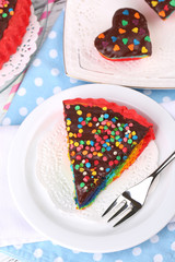 Delicious rainbow cakes on plate, on table, on bright