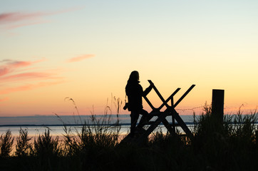 Silhouette of a woman on a stile at twilight time