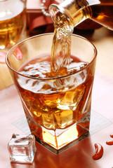 versare il whisky nel bicchiere di vetro
