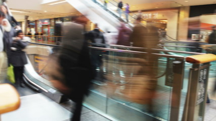 Time Lapse Sequence Of Shoppers On Escalators In Mall