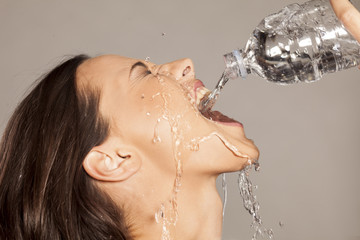 girl pouring water into her mouth from a plastic bottle