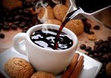 versare il caffè caldo nella tazzina bianca poster