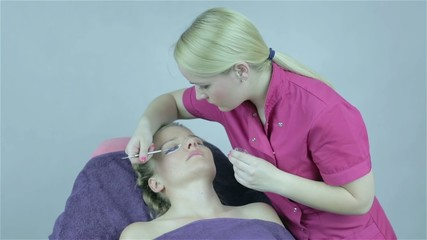 Lashes tinting treatment with henna dye by cosmetician.