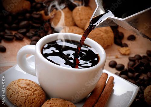 Poster versare il caffè caldo nella tazzina bianca