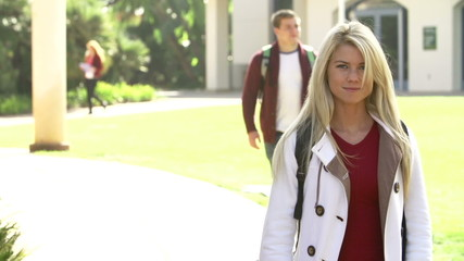 Female Student Walking Outdoors On University Campus