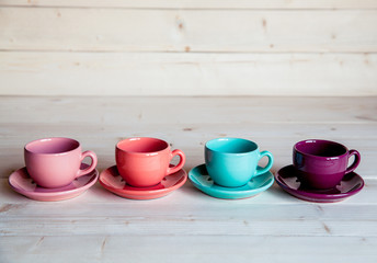 Colorful coffee cups on wooden table