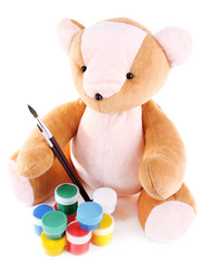 Toy bear and paints isolated on white