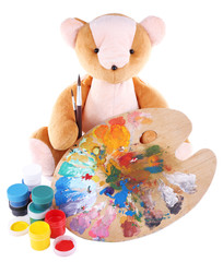 Toy bear, palette and paints isolated on white