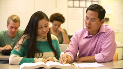 Female High School Student With Teacher Discussing Textbook