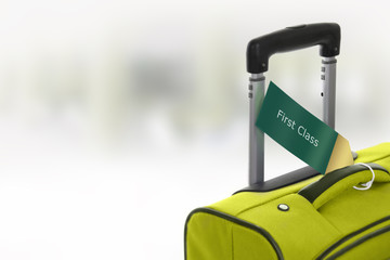 First Class. Green suitcase with label at airport.