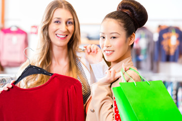 women buying fashion clothes in shop or store