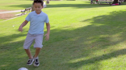 Young Boy Playing Football In Park