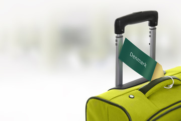 Denmark. Green suitcase with label at airport.