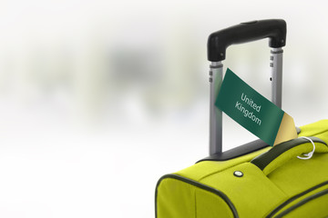 United Kingdom. Green suitcase with label at airport.