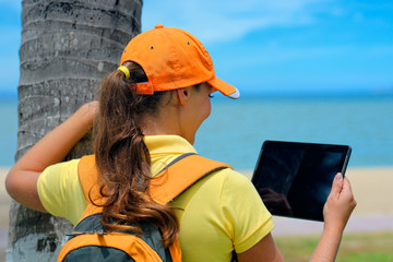 Side view of young woman in cap on the outdoor with  tablet