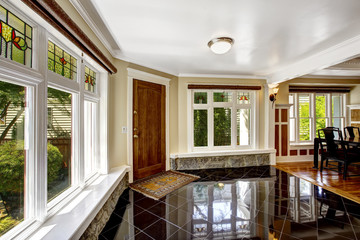Foyer with black shiny tile floor and stone trim under the windo