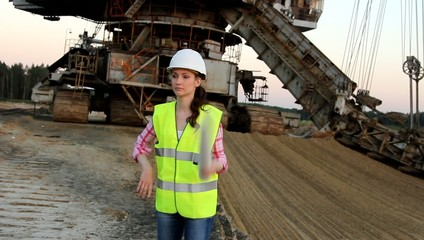 The girl twists drawings in a roll against the big excavator