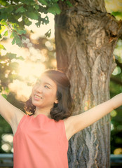 木陰で腕を広げる女性