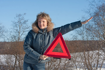 Woman with a warning triangle in sunny winter day above broken c