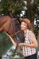 Woman in hat embrace brown horse