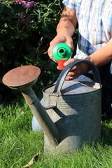 Mann füllt Flüssigdünger in Zinkkanne, Garten
