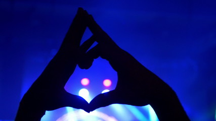 Hands forming heart at live music concert, festival