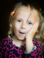 Cute little girl smiling over dark background. S