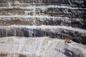 Wall of a modern diamond mine and a big yellow machinery