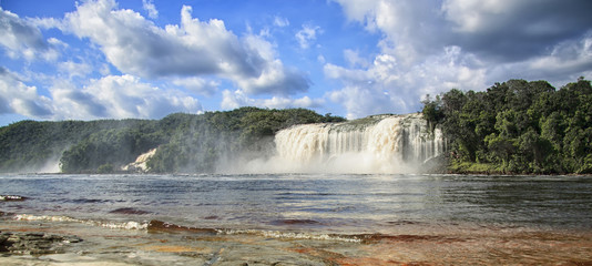 Beautiful powerful waterfall flowing into the lake on a bright s