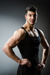 Muscular man posing in dark studio
