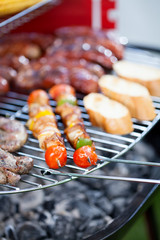 Sausages, bread and shashliks on grill