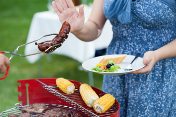 Woman on a diet during barbecue