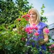 Frau mit rosa Rosen im Garten