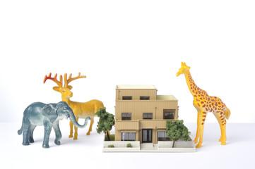 住宅模型と巨大な動物