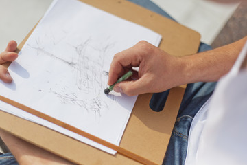 man draws a pastel drawing, closeup