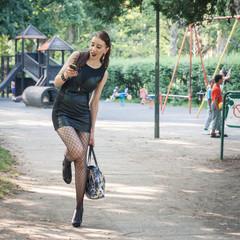 Pretty goth girl using phone in a city park