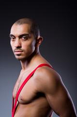 Wrestler in red dress against dark background