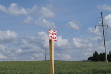 Информационный столб на фоне пшеничного поля