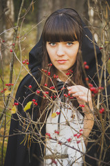 girl witch in a black cloak in the forest