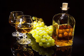 Bottle of brandy and two glasses and grapes