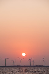wind turbines and sun in colorful sky