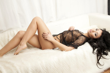 Young slim sexy woman in lingerie on the white fur