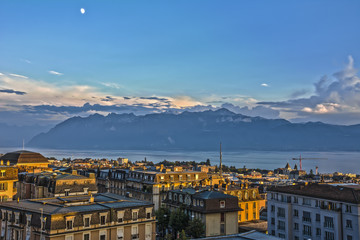 View over Lausanne roofs at sunset with lake Geneva and Alps