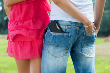 Young couple with mobile in the pocket.